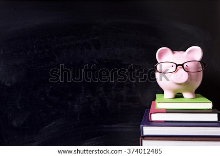 Piggy bank, glasses, blackboard background, college fund saving concept, copy space - stock photo
