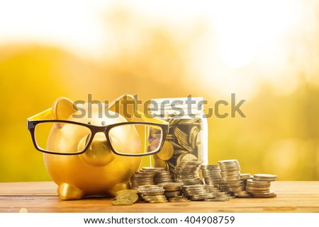 Piggy bank gold color and stack of money in the garden outside. - stock photo