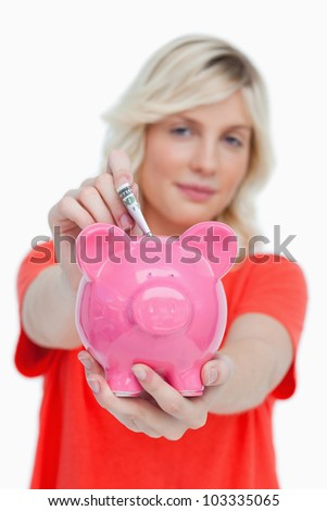 Piggy bank held by a woman and receiving notes against a white background - stock photo