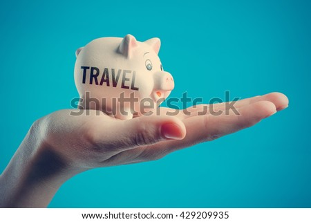 Piggy bank in a human hand with inscription TRAVEL on a blue background - stock photo
