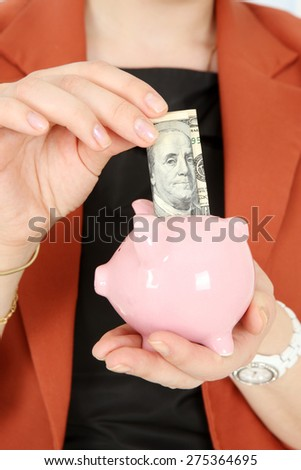 Piggy Bank in hands with money being put in
