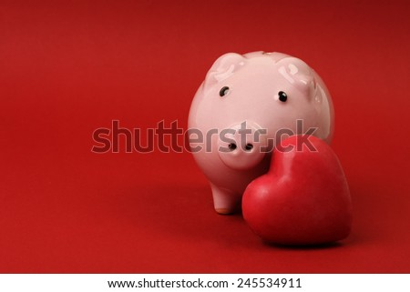 Piggy bank in love with red heart on red background - stock photo