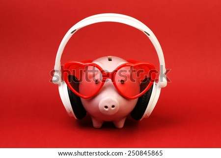 Piggy bank in love with red heart sunglasses and white headset standing on red background - stock photo