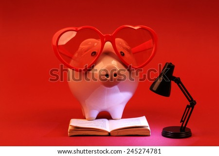 Piggy bank in love with red heart sunglasses reading a book and shining black lamp on red background - stock photo