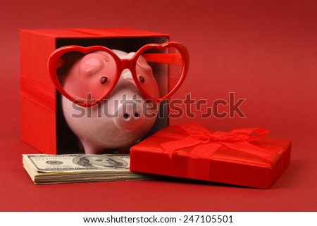 Piggy bank in love with red heart sunglasses standing in gift box with ribbon and with stack of money american hundred dollar bills on red background - stock photo