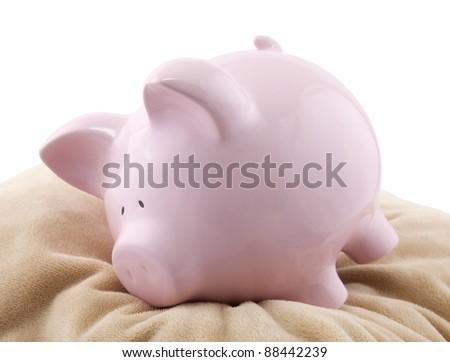 Piggy bank lying down on a pillow - stock photo