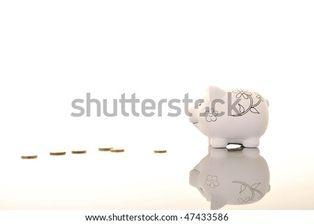 piggy bank object with coins on reflective surface - stock photo
