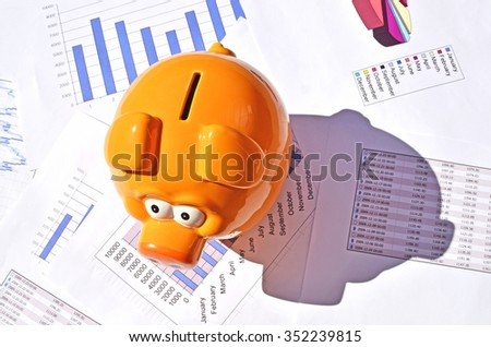 Piggy bank on a financial report - stock photo