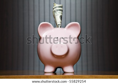 Piggy bank on a table with dollar sticking out of it���¢��������s top - stock photo