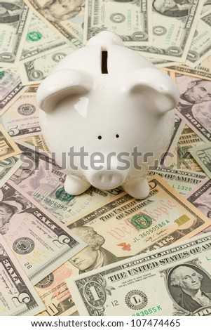 Piggy bank on 1 ,5, 10 and 20 dollar bills - stock photo