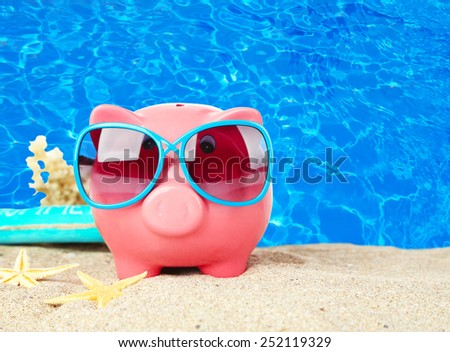 Piggy bank on beach background - stock photo