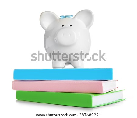 Piggy bank on books, isolated on white