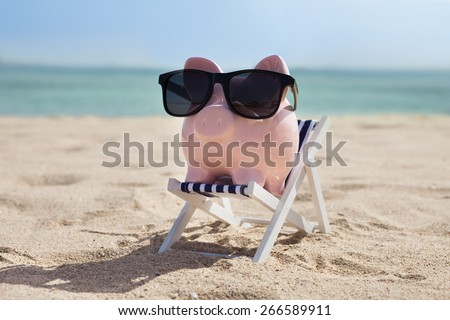 Piggy Bank On Deckchair With Sunglasses  - stock photo