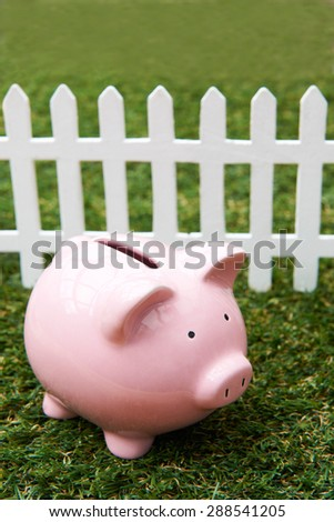 Piggy Bank On Grass With White Fence