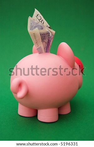 Piggy bank on green - shallow dof - stock photo