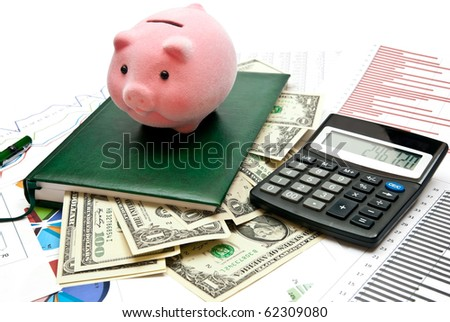 Piggy bank on office table with charts, money, calculator and notebook - stock photo