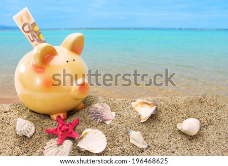 Piggy bank on sand with summer sea background - stock photo