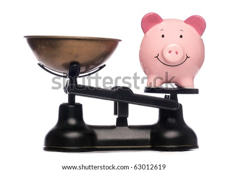 piggy bank on scales studio cutout - stock photo