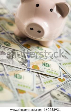 Piggy Bank on Stacks of Newly Designed One Hundred Dollar Bills - stock photo
