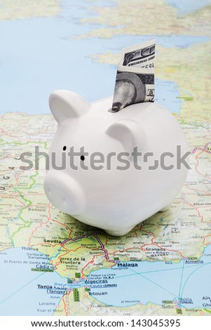 Piggy bank on top of a map symbol of world economy or holiday savings - stock photo