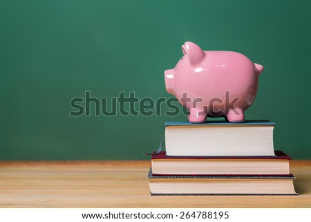 Piggy bank on top of books with chalkboard, cost of education theme - stock photo
