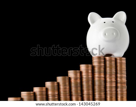 Piggy bank on top of stack of coins showing growth - stock photo