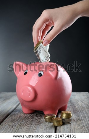 Piggy bank on wooden table on grey background