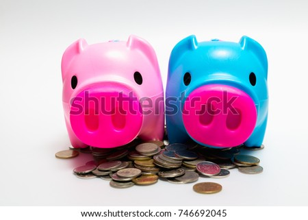 Piggy bank over a lot of coins on white background