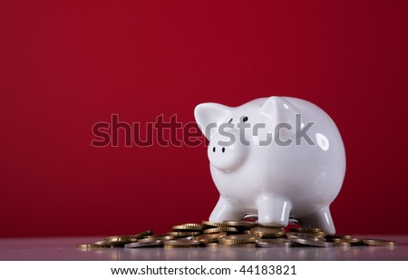Piggy bank over a lot of coins with a red background - stock photo