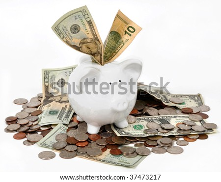Piggy bank over flowing with money - stock photo