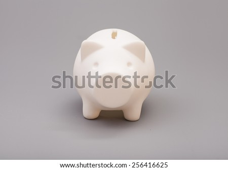 Piggy bank over gray background - stock photo