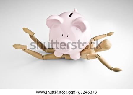 Piggy bank placed on manikin - stock photo