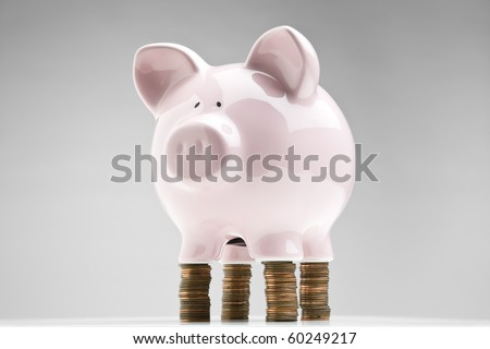Piggy bank placed on stacks of pennies - stock photo