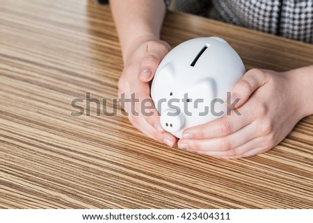 Piggy bank protected by hands - stock photo