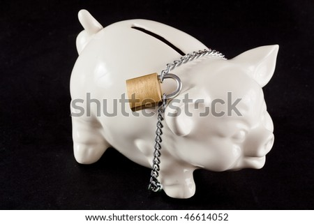 Piggy bank protected by padlock and chain - stock photo