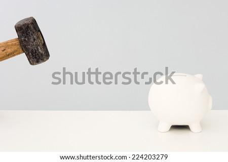 Piggy bank running away from hammer - stock photo