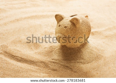 Piggy bank sculpted in sand on sandy beach - stock photo