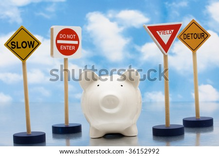 Piggy bank sitting next to a road signs on a sky background, risky investments - stock photo