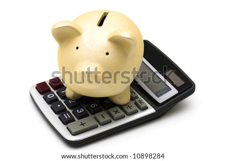 Piggy bank sitting on a calculator isolated on white - stock photo