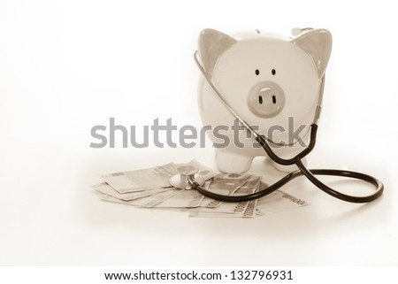 Piggy bank sitting on pile of dollars with stethoscope in black and white - stock photo