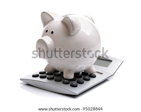 Piggy bank sitting on top of a calculator concept for calculating finance - stock photo