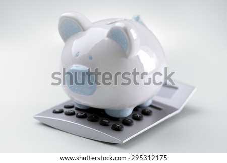 Piggy bank sitting on top of a calculator concept for calculating finance, accounting and tax - stock photo