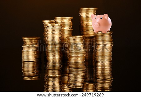 Piggy bank standing on stack of coins isolated on black - stock photo