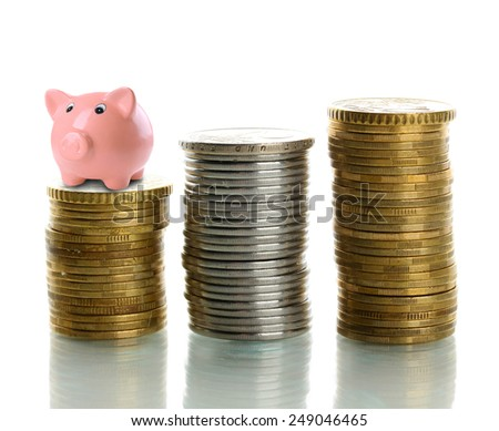Piggy bank standing on stack of coins isolated on white - stock photo