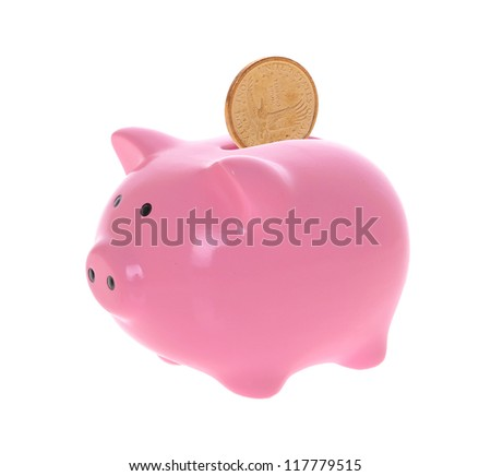 Piggy bank style money box with coins falling into slot isolated on a white studio background