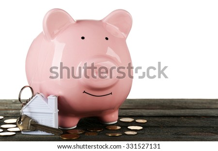 Piggy bank style money box with key on wooden table, isolated on white - stock photo