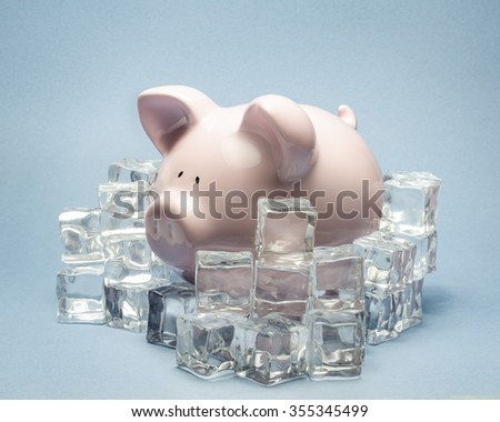 piggy bank surrounded by ice cubes  - stock photo