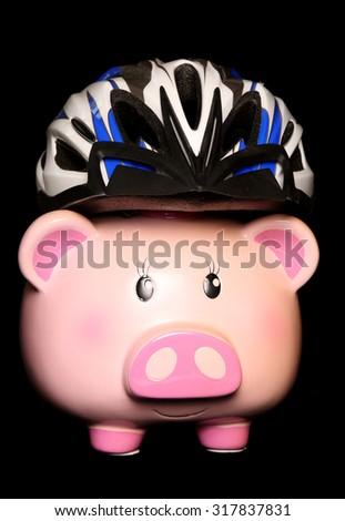 Piggy bank wearing a cycling helmet cutout - stock photo
