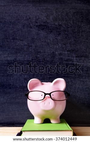 Piggy bank wearing glasses, blackboard background, college fund concept, vertical - stock photo