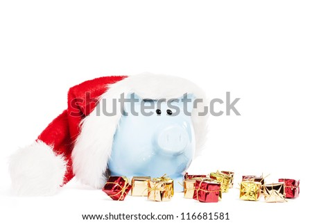 piggy bank wearing santas hat with tiny christmas presents on white background - stock photo